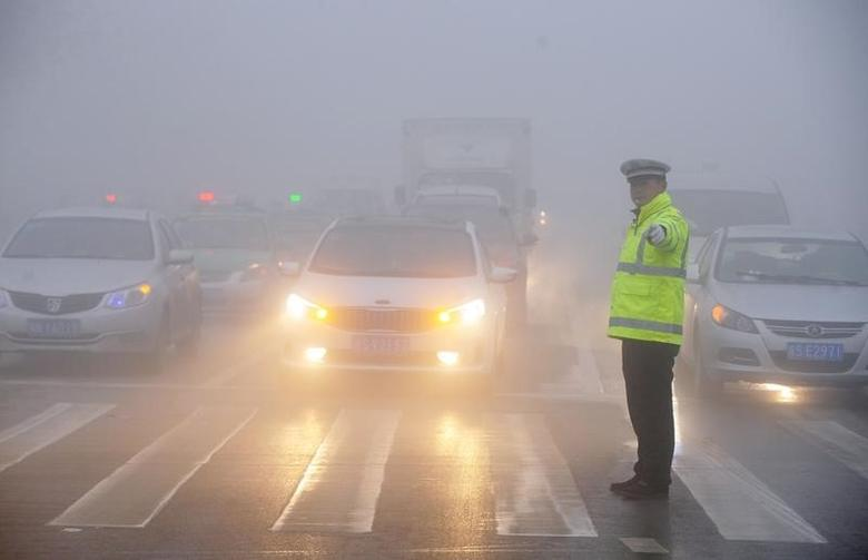 A traffic police works among heavy smog during a polluted day in Bozhou, Anhui province, China, February 5, 2017. REUTERS/Stringer ATTENTION EDITORS - THIS PICTURE WAS PROVIDED BY A THIRD PARTY. EDITORIAL USE ONLY. CHINA OUT. NO COMMERCIAL OR EDITORIAL SALES IN CHINA. - RTX2ZO49