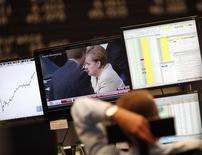 Трейдер на фондовой бирже во Франкфурте-на-Майне смотрит выпуск новостей с сюжетом о канцлере Германии Ангеле Меркель. 29 сентября 2011 года. Наличие серьезного конкурента у канцлера Германии Ангелы Меркель на предстоящих выборах заставляет глобальных инвесторов рассматривать возможность неожиданного исхода голосования, чреватого исчезновением одной из главных политических констант, сохранявшейся в годы турбулентности в еврозоне, но также сулящего конец режиму жесткой экономии в Европе. REUTERS/Ralph Orlowski