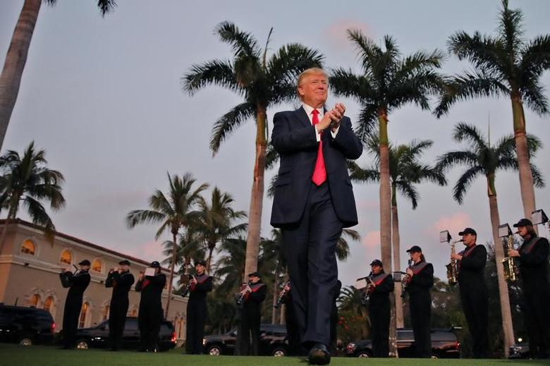 U.S. President Donald Trump applauses as a marching band performs while he arrives at Trump International Golf club to watch the Super Bowl LI between New England Patriots and Atlanta Falcons in West Palm Beach, Florida, U.S.,  February 5, 2017. REUTERS/Carlos Barria