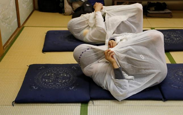 2月4日、頭からつま先まで白い布に袋状に包まれ、ゆっくりゆらされることで出産後の肩や腰の痛みをやわらげる、という最新の健康法「おとなまき」が静かなブームを呼んでいる(2017年 ロイター/Toru Hanai)