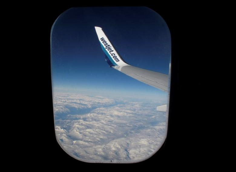 Snow covered mountains are seen under the wing of a WestJet commercial flight on route from Vancouver to Calgary November 23, 2010.   REUTERS/Mike Blake/File Photo
