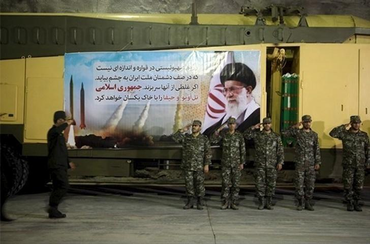 Members of Iran's Islamic Revolutionary Guard Corps (IRGC) Aerospace Force salute at an underground missile base with launcher units in an undisclosed location in this undated handout photo courtesy of Fars News. REUTERS/farsnews.com/Handout via Reuters/File Photo
