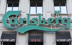 Логотип Carlsberg над входом в паб в Брюсселе. Продажи Carlsberg снизились и не оправдали ожиданий во всех трёх регионах, где представлена датская компания, в четвёртом квартале, и производитель пива сообщил, что ужесточение норм, регулирующих продажу алкогольных напитков в России, отрицательно скажется на прибыли в 2017 году.    REUTERS/Yves Herman