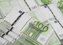 Пачки банкнот в 100 евро в штаб-квартире компании GSA в Вене. 22 июля 2013 года. Политическая неопределенность в преддверии выборов в Европе заставила обеспокоенных инвесторов продавать евро и продолжила оказывать давление на облигации стран еврозоны с более низким рейтингом в среду, в то время как цена на считающееся безопасным активом золото достигла трехмесячных пиков. REUTERS/Leonhard Foeger/Files