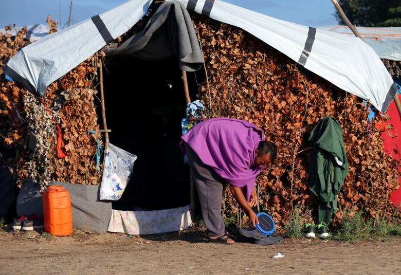 A refugee cleans his tent in a makeshift camp on the Hungary-Serbia border, on the Serbian side of a transit zone set up by Hungarian authorities to filter refugees at Roszke, Hungary, September 2, 2016. REUTERS/Laszlo Balogh