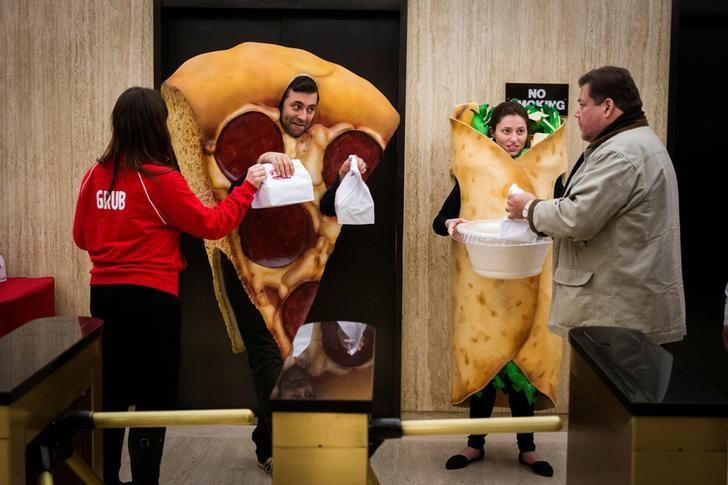 FILE PHOTO -  People dressed in food-themed costumes give away donuts to people headed to the floor of the New York Stock Exchange to celebrate the IPO of GrubHub, in New York April 4, 2014.   REUTERS/Lucas Jackson/File Photo