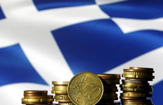 2月7日、ギリシャ国債の民間投資家は、デフォルト(債務不履行)はもう二度と起きないという5年前に欧州当局が表明した約束を信用できなくなっているようだ。写真はユーロ硬貨とギリシャ国旗。ボスニア・ヘルツェゴビナのゼニツァで2015年6月撮影(2017年 ロイター/Dado Ruvic)
