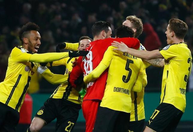 2月8日、サッカーのドイツ杯でドルトムントはヘルタをPK戦の末に下してベスト8進出を果たした。写真は勝利を喜ぶドルトムントの選手たち(2017年 ロイター/Wolfgang Rattay)