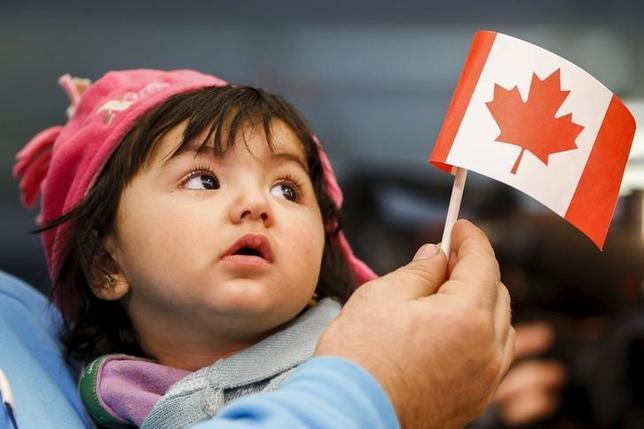 2月9日、カナダ統計局によると、2016年の人口は3520万人で、年間の平均伸び率は主要7カ国(G7)最大の1.0%だった。移民が押し上げ要因。写真はオンタリオ州トロント国際空港でシリアから到着した難民親子。2015年12月撮影(2017年 ロイター/Mark Blinch)
