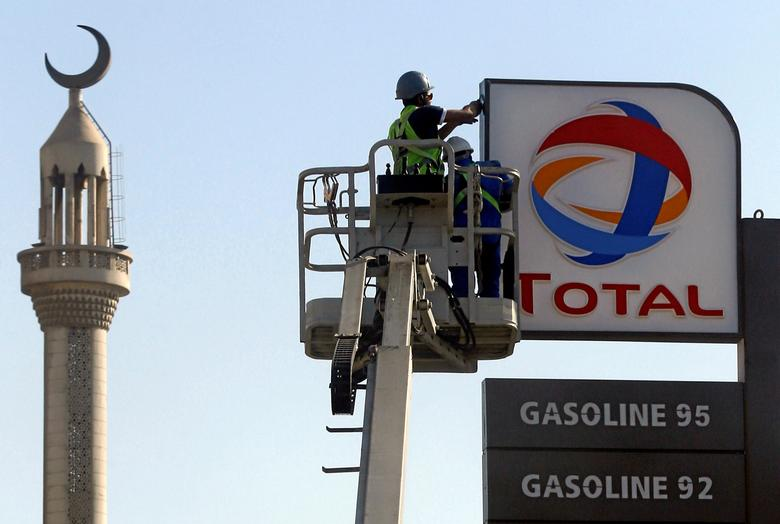 FILE PHOTO: Workers fix a sign for oil giant Total at a petrol station in Cairo, Egypt, October 13, 2016.  REUTERS/Amr Abdallah Dalsh/File Photo