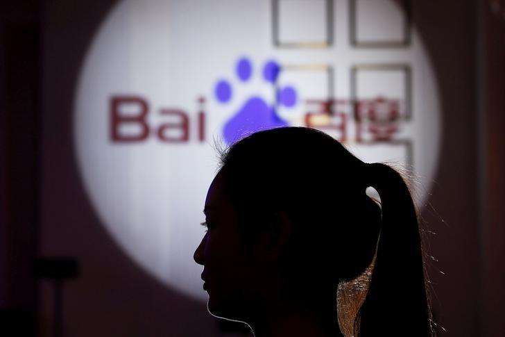A woman is silhouetted against the Baidu logo at a new product launch from Baidu, in Shanghai, China, November 26, 2015. REUTERS/Aly Song/File Photo