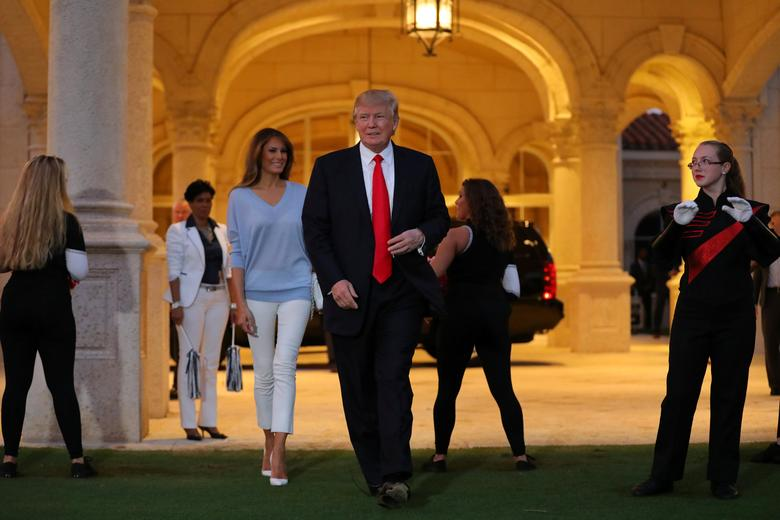 U.S. President Donald Trump and First Lady Melania Trump greet a marching band as they arrive at Trump International Golf club to watch the Super Bowl LI between New England Patriots and Atlanta Falcons in West Palm Beach, Florida, U.S.,  February 5, 2017. REUTERS/Carlos Barria