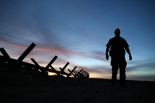 U.S. border patrol agent Alessio Faccin  walks along the border fence separating Mexican from the United States near Calexico, California, U.S. February 8, 2017. REUTERS/Mike Blake