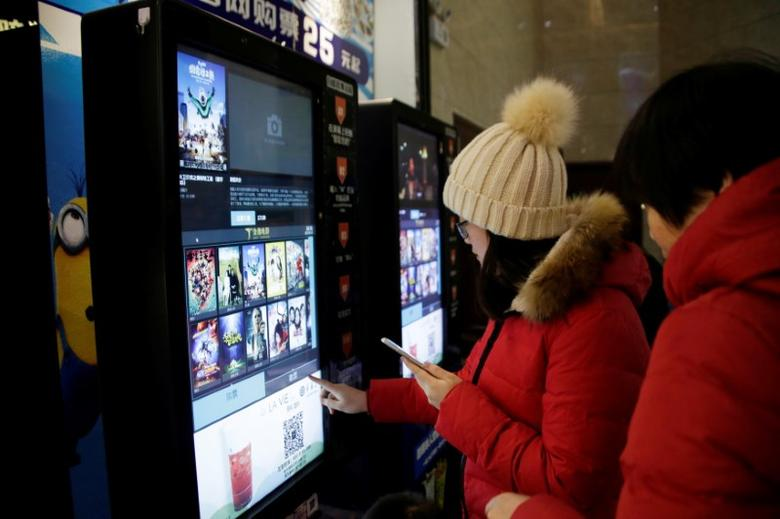 People print movie tickets from a machine at a cinema in Tianjin, China, January 13, 2017. REUTERS/Jason Lee