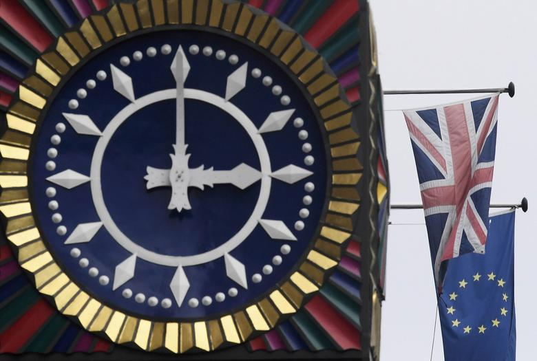 The British Union flag and the European Union flag are seen flying behind a clock in the City of London, Britain, January 16 , 2017. REUTERS/Toby Melville
