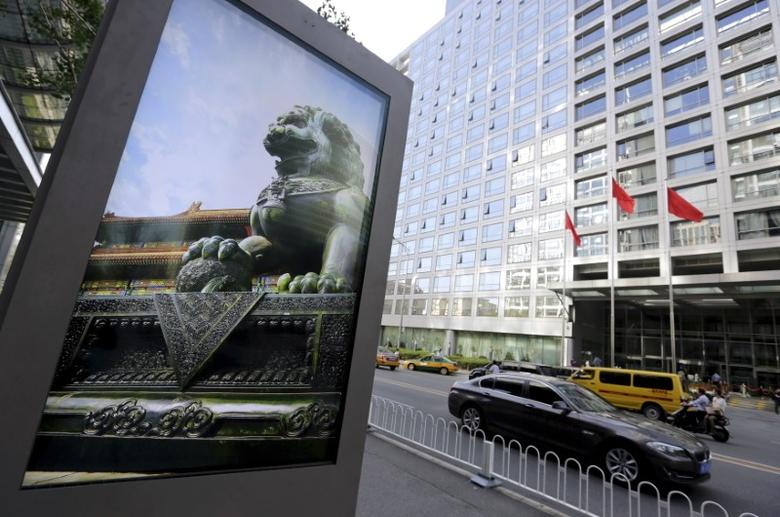 An advertising board (L) showing a Chinese stone lion is pictured near an entrance to the headquarters (R) of China Securities Regulatory Commission (CSRC), in Beijing, China, September 7, 2015.   REUTERS/Jason Lee/File Photo
