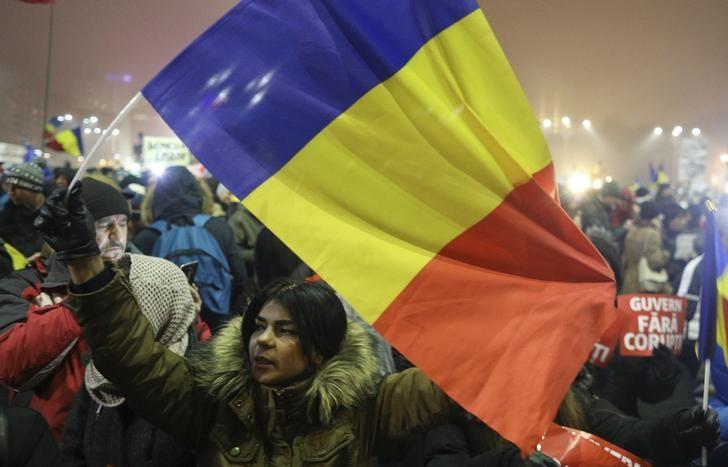 A woman waves a Romanian flag during a protest of thousands against their government in Bucharest, Romania, February 6, 2017. REUTERS/Stoyan Nenov