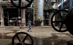 Un trabajador camina por tuberías de petroleo en Wuhan, provincia de Hubei, China. 23 de marzo 2012.Las compras de materias primas clave de China se mantuvieron cerca de niveles récord el mes pasado, pese al extenso feriado por el Año Nuevo Lunar, ya que las empresas de servicios públicos, las siderúrgicas y las refinerías elevaron la demanda de insumos como carbón, mineral de hierro y crudo. REUTERS/Stringer/File Photo - RTSLRAT