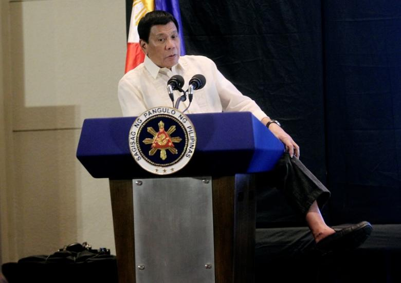 Philippine President Rodrigo Duterte shows he is not wearing socks while speaking at an economic forum in Davao city, in southern Philippines February 10, 2017. REUTERS/Lean Daval Jr