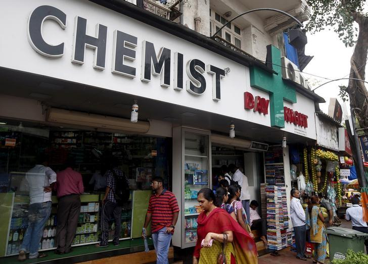 FILE PHOTO: People walk past a chemist's shop at a market in Mumbai, India June 25, 2015. REUTERS/Shailesh Andrade/File Photo