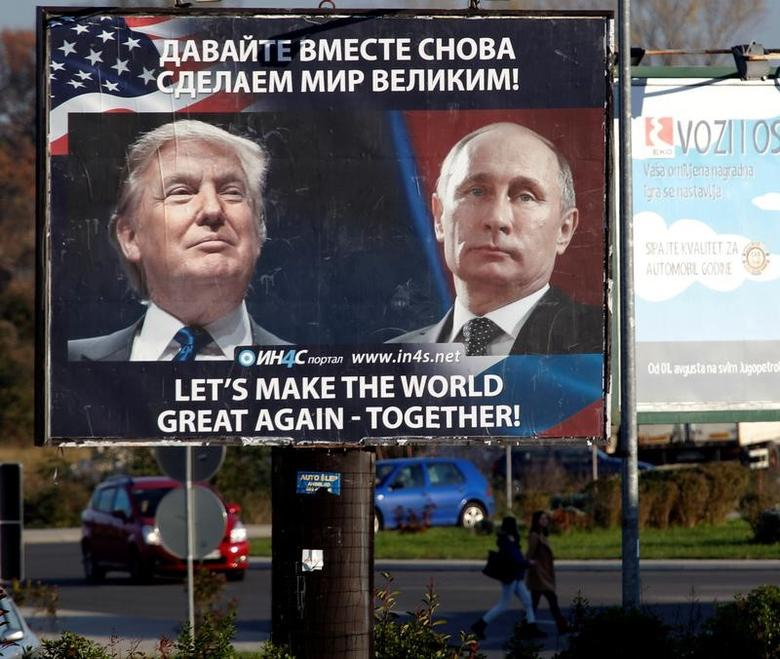 Pedestrians cross the street behind a billboard showing a pictures of  US president-elect Donald Trump and Russian President Vladimir Putin in Danilovgrad, Montenegro, November 16. 2016. REUTERS/Stevo Vasiljevic