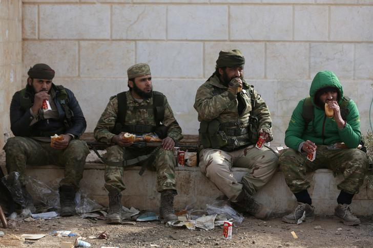 Rebel fighters eat while resting on the outskirts of the northern Syrian town of al-Bab, Syria February 8, 2017. REUTERS/Khalil Ashawi