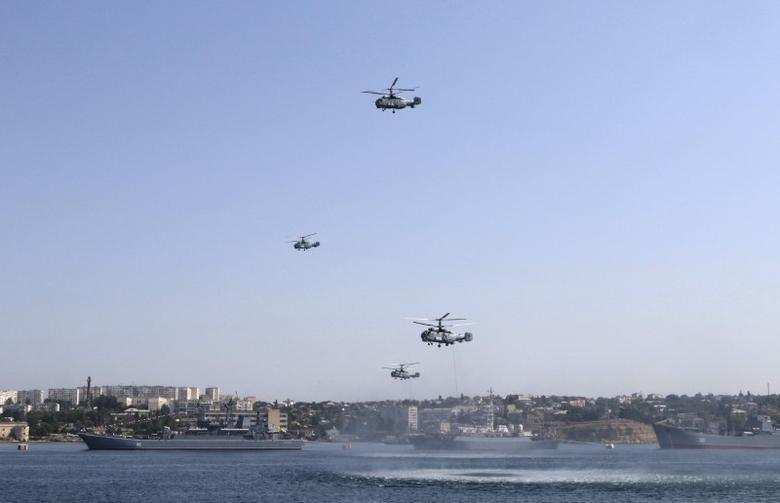Russian military helicopters fly in formation, with warships seen on the water, during celebrations for Navy Day in the Black Sea port of Sevastopol, Crimea, July 26, 2015. REUTERS/Pavel Rebrov/File Photo