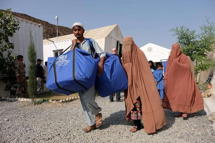 An Afghan family, who were living as refugees in Pakistan, carries bundles of supplies at a humanitarian aid station in Torkham, Afghanistan, October 22, 2016. REUTERS/Josh Smith/Files