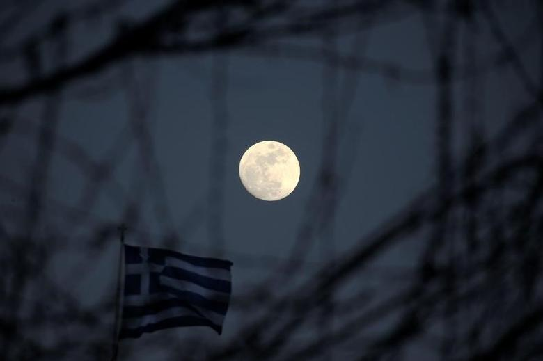 The moon rises next to a fluttering Greek national flag in Athens, Greece February 9, 2017. REUTERS/Alkis Konstantinidis