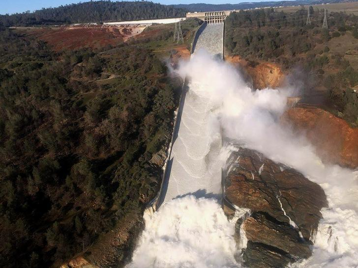 A damaged spillway with eroded hillside is seen in an aerial photo taken over the Oroville Dam in Oroville, California, U.S. February 11, 2017.  California Department of Water Resources/William Croyle/Handout via REUTERS/File Photo