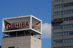 Логотип Toshiba Corp на здании в Токио. Корпорация Toshiba сообщила во вторник, что намерена списать 712,5 миллиарда иен ($6,28 миллиарда)в ядерном подразделении в США, из-за чего компания потеряет часть акционерного капитала и завершит год с убытком.  REUTERS/Toru Hanai