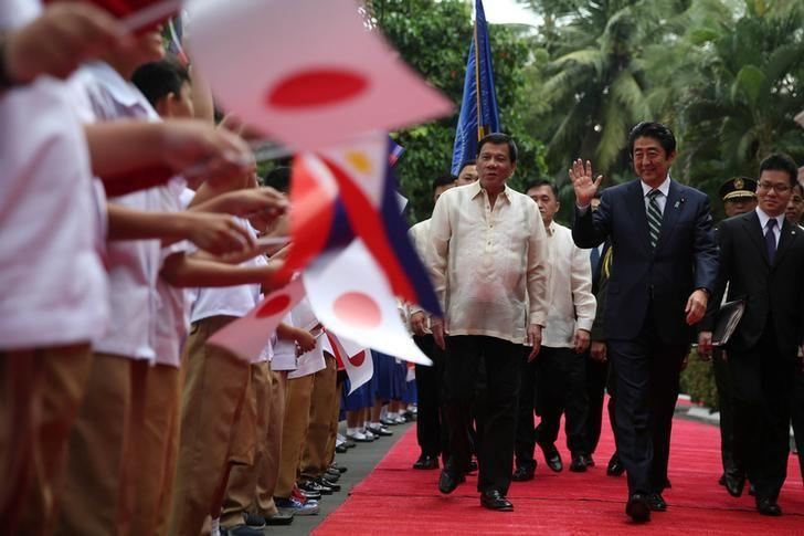 President Rodrigo Duterte joins Japan Prime Minister Shinzo Abe (R) as he interacts with the pupils waving the Japan and Philippine flags before entering the Malacanang presidential palace in metro Manila, Philippines January 12, 2017. Malacanang Photo/ Handout via Reuters