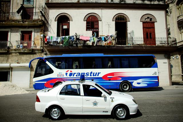 A Chinese-made Geely police car passes by a parked Yutong bus, which is also made in China, in Havana, Cuba, February 10, 2017. REUTERS/Alexandre Meneghini