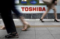El grupo japonés Toshiba dijo el martes tras un día de retrasos y confusión que prevé contabilizar un impacto de 6.300 millones de dólares a partir de su filial estadounidense de energía nuclear, un ajuste que borra recursos propios y que llevará a la compañía a sufrir pérdidas anuales. En la imagen, peatones pasan por delante de un logo de Toshiba Corp delante de una tienda de electrónica en Tokio, el 14 de septiembre de 2015.   REUTERS/Toru Hanai/File Photo