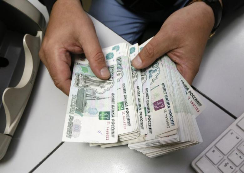 An employee counts Russian ruble banknotes at a private company's office in Krasnoyarsk, Siberia, December 17, 2014. REUTERS/Ilya Naymushin
