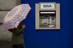 El Tribunal Supremo ha asumido la jurisprudencia de la sentencia del Tribunal de Justicia de la Unión Europea que obliga a los bancos españoles a pagar el 100 por cien de las cantidades cobradas de más a los clientes con cláusulas suelo declaradas nulas. En la imagen de archivo, una mujer que se cobija bajo un paraguas pasa ante un cajero de BBVA en Madrid, el 4 de abril de 2016. REUTERS/Andrea Comas