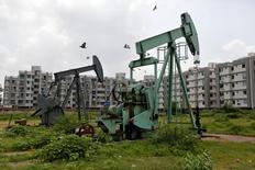 Нефтяные насосы на месторождении компании Oil and Natural Gas Corp  ядом с Ахмедабадом, Индия.  Цены нанефтьснизились на торгах в среду на фоне превысившего прогнозы роста запасов в США и несмотря на рекордное соблюдение пакта ОПЕК.  REUTERS/Amit Dave