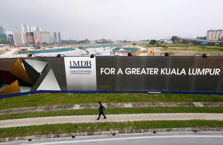 A man walks past a 1 Malaysia Development Berhad (1MDB) billboard at the funds flagship Tun Razak Exchange development in Kuala Lumpur, March 1, 2015. REUTERS/Olivia Harris/File Photo