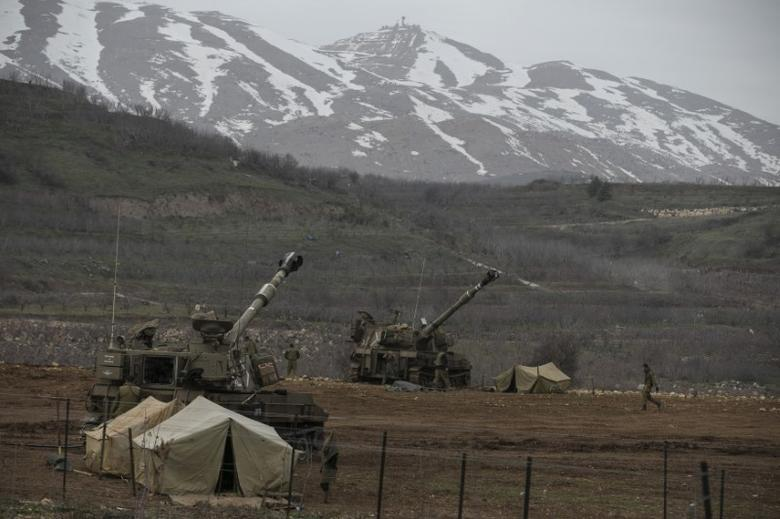 Israeli soldiers walk near mobile artillery units near the border with Syria in the Golan Heights January 27, 2015. REUTERS/Baz Ratner