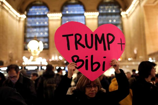 A demonstrator holds a sign during a ''Muslim and Jewish Solidarity'' protest against the policies of U.S. President Donald Trump and Israeli Prime Minister Benjamin Netanyahu at Grand Central Terminal in New York City, U.S., February 15, 2017. REUTERS/Mike Segar