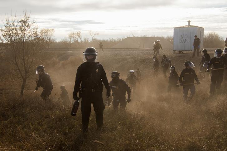 Riot police clear marchers from a secondary road outside a Dakota Access Pipeline (DAPL) worker camp using rubber bullets, pepper spray, tasers and arrests in Cannon Ball, North Dakota, U.S., November 15, 2016. Amber Bracken/Courtesy of World Press Photo Foundation/Handout via REUTERS/Files