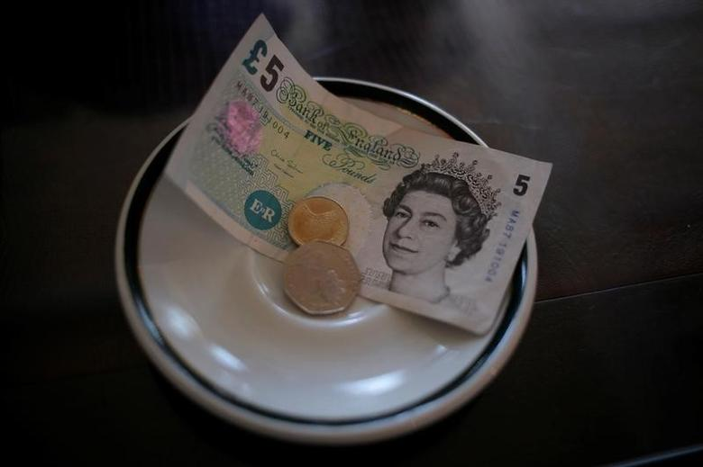 An English five Pound note and coins are seen at a restaurant in the British overseas territory of Gibraltar, July 21, 2016. REUTERS/Jon Nazca - RTSJ3TN