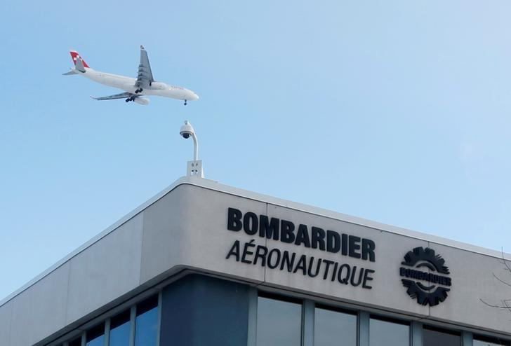 FILE PHOTO - A plane flies over a Bombardier plant in Montreal, Quebec, Canada on January 21, 2014.   REUTERS/Christinne Muschi/File Photo