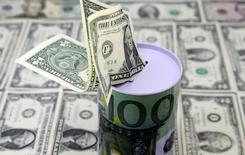 Долларовые банкноты. Доллар остаётся вблизи недельного минимума к корзине основных валют в пятницу, поскольку оптимистичные экономические данные не повляили на доходность гособлигаций США из-за опасений, что торговая политика США ограничит попытки американской валюты к восстановлению. REUTERS/Dado Ruvic/Illustration