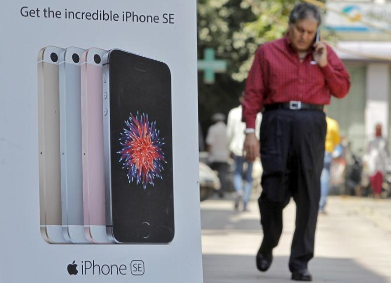 A man speaks on his mobile phone as he walks past an Apple iPhone SE advertisement billboard in a street in New Delhi, India, April 25, 2016. REUTERS/Anindito Mukherjee