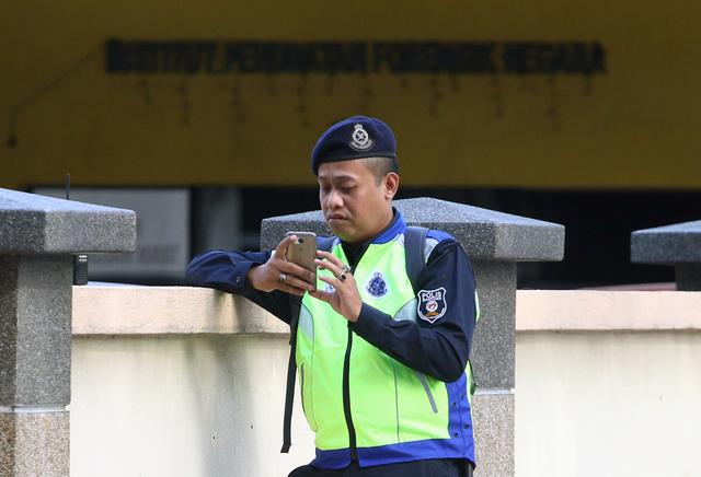A police officer looks at his mobile phone as he stands guard outside the morgue at Kuala Lumpur General Hospital where Kim Jong Nam's body is held for autopsy in Malaysia, February 17, 2017. REUTERS/Athit Perawongmetha