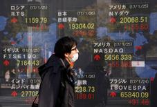 En la imagen, un hombra pasa ante un letrero electrónico que muestra la cotización del Nikkei, el Dow Jones y otros índices en una casa de valores de Tokio, el 26 de enero de 2017. Las acciones japonesas bajaron el viernes ante la preocupación del mercado por el avance del yen, mientras que el sector de finanzas se debilitó por la caída de rendimientos de la deuda estadounidense tras los comentarios de un funcionario de la Reserva Federal que reforzaron la percepción de una política monetaria expansiva. REUTERS/Kim Kyung-Hoon
