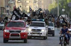 مقاتلون من تنظيم الدولة الاسلامية أثناء عرض عسكري في الرقة - صورة من أرشيف رويترز.