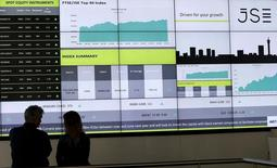 People chat in front of an electronic board displaying movements in major indices at the Johannesburg Stock Exchange building in Sandton Johannesburg July 9, 2015.    REUTERS/Siphiwe Sibeko