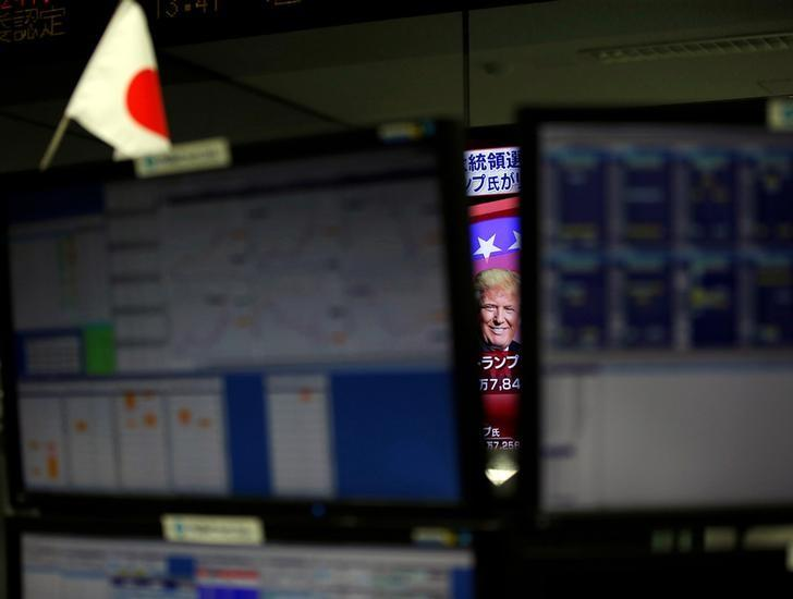 U.S. Republican presidential nominee Donald Trump is seen between monitors on TV news at a foreign exchange trading company in Tokyo, Japan, November 9, 2016. REUTERS/Toru Hanai/Files